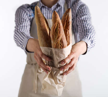 Bakers hands hold fresh bread isolated on white background.