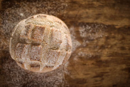 Round loaf of home made bread on wooden background