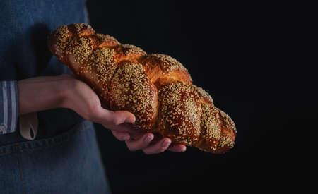 artisan bakery: Bakers hands hold fresh bread over dark background. Stock Photo