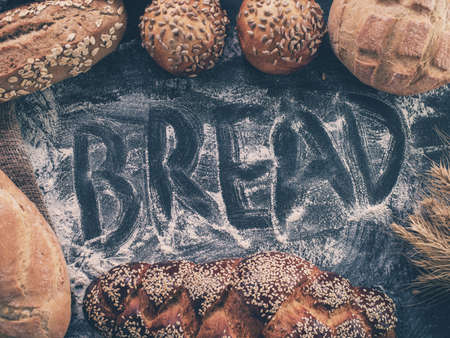 artisan bakery: Background with fresh bread and inscription Bread on flour. Retro toned image. Hipster color. Stock Photo