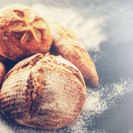 Homemade fresh bread on the dark table. Retro vintage film toned Stock Photo