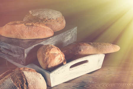 Different kinds of bread on wooden table.