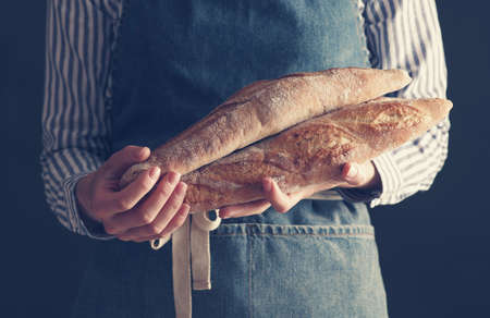 Bakers hands hold fresh baguettes.
