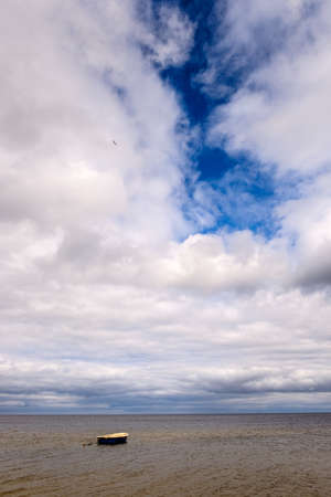 Sea view with a boat. Cloudy weather. Stock Photo