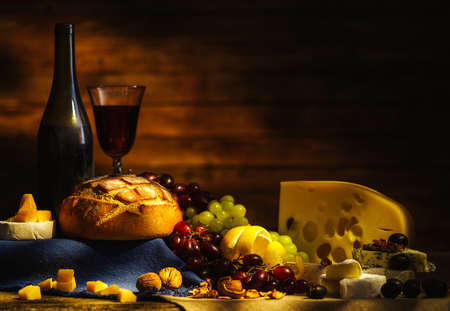 Still life with wine, grapes, bread and various sorts of cheese. Copyspace for text.
