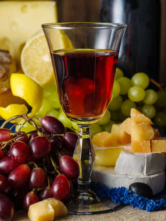 A glass of red wine with cheese and grapes on the table. Stock Photo