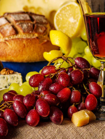 Red Grapes with a glass of wine and fruits on the table Stock Photo