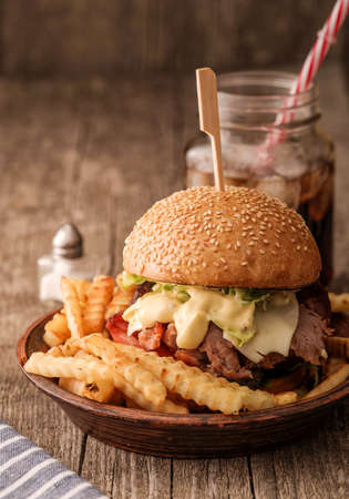 Freshly cooked homemade burger with chopped beef, cheese and fresh herbs