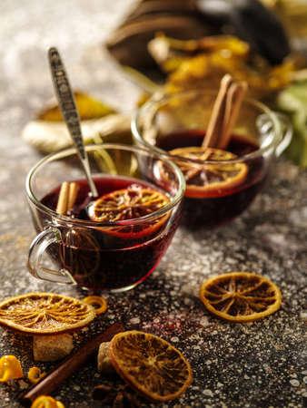 Hot mulled wine with orange, cinnamon, cardamom and anise on darken background.