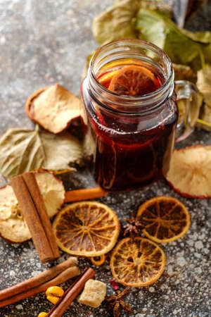 Hot mulled wine with orange, cinnamon, cardamom and anise on darken background. Autumn concept. Stock Photo