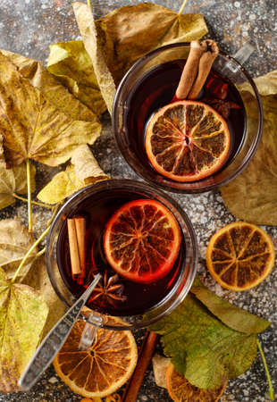 Hot mulled wine with orange, cinnamon, cardamom and anise on darken background. Autumn concept. Top view.