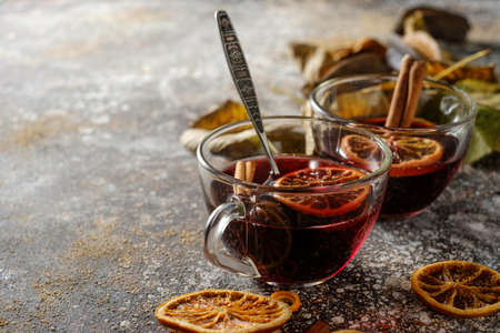 Hot mulled wine with orange, cinnamon, cardamom and anise on darken background. Autumn concept. Imagens