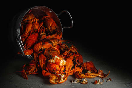 Many crawfish in an aluminum pan on a dark background