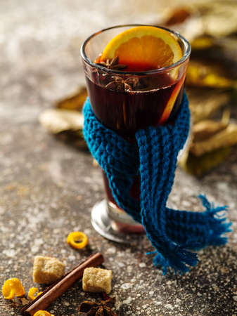 Christmas hot mulled wine with orange, cinnamon, cardamom and anise on wooden background.