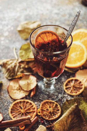 Hot mulled wine with orange, cinnamon, cardamom and anise on darken background. Autumn concept. Banco de Imagens