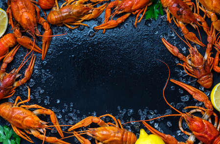 Fresh boiled crawfish with lemons and greens on a dark table with ice. Copyspace for text. Top view.