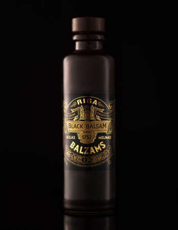 MINSK, BELARUS - AUGUST 14, 2017: Herb hard liqueur Riga Black Balsam bottle against black background. It is a traditional Latvian herbal liqueur made with many natural ingredients.