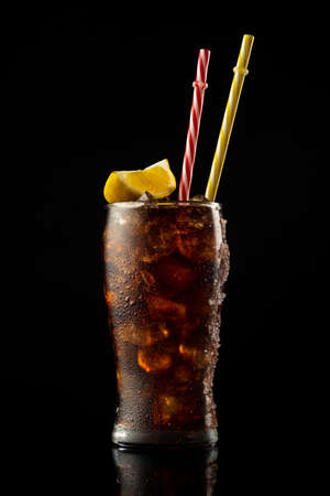 Glass cola with ice and straw. Cold glass of cola with lemon.