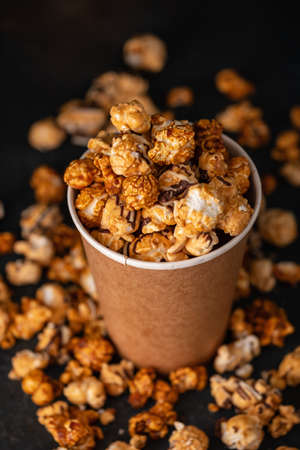 Diverse Popcorn in a paper cup against a dark background. Top view.