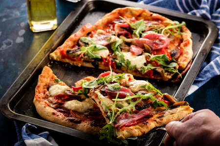 Pizza with prosciutto, mozzarella, mushroom and rocket salad with spices on blue background. A human hand takes a piece of pizza.