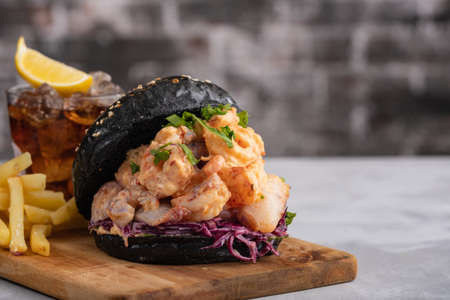 Black burger with fish and shrimps. Fishburger with prawns.