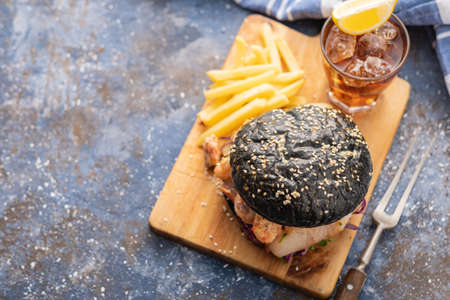 Black burger with fish and shrimps. Fishburger with prawns. Top view. Stock Photo