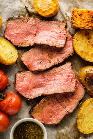 Sliced Roast beef on cutting board with grilled vegetables. View from above.