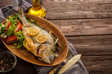 Grilled Dorado with lemon, thyme, rosemary and fresh salad on the wooden table