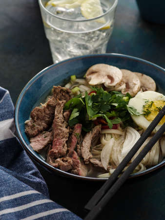 Asian ramen soup with beef, egg, chives, mushrooms in bowl