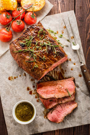 Sliced Roast beef on white paper on wooden table with grilled vegetables Stock Photo