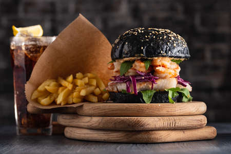 Black burger with fish and shrimps. Fishburger with prawns and French Fries.