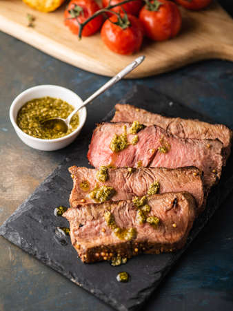 Sliced Roast beef on cutting board with grilled vegetables