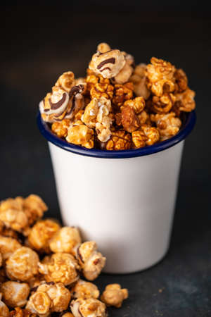 A variety of Popcorn in a white cup on a dark background Stock Photo