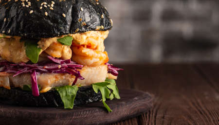 Closeup of Black burger with fish and shrimps. Fishburger with prawns. Stock Photo