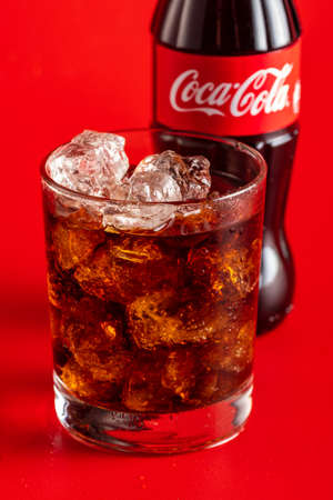 MINSK, BELARUS - APRIL 14, 2018: Classic bottle of Coca-Cola and glass with ice and beverage on red background. Coca Cola drinks are produced and manufactured by The Coca-Cola Company. Editorial