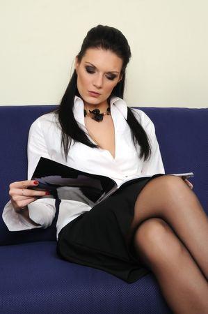 pretty young girl reading magazine on sofa photo