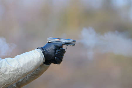 Close-up Photo of a pistol shooting with two hands, the shells emanating from the shutter and blue smoke on a blurred background.