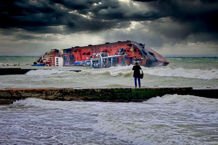 After a severe storm, the tanker was shipwrecked on the popular beach of Odessa, Ukraine. The ship lies on its side directly on the breakwater. Close-up dramatic photo.
