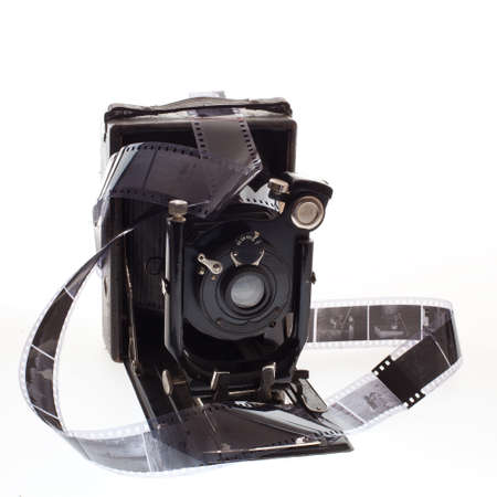 historic old photo camera with negatives on white background