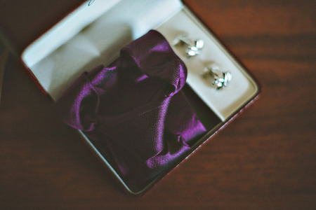 cuff links: jeweler black cuff links of the groom a buttonhole from a rose and blue bow-tie. Wedding flowers, rings, boutonniere and tie are on the table