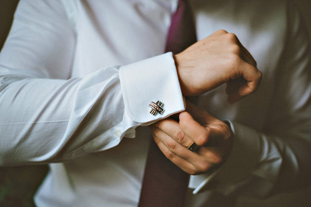 close up of a hand man how wears white shirt and cufflink. The groom button cufflinks on a white shirt Stock Photo