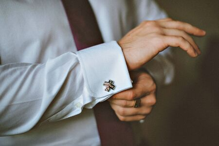 french cuffs: close up of a hand man how wears white shirt and cufflink. The groom button cufflinks on a white shirt Stock Photo