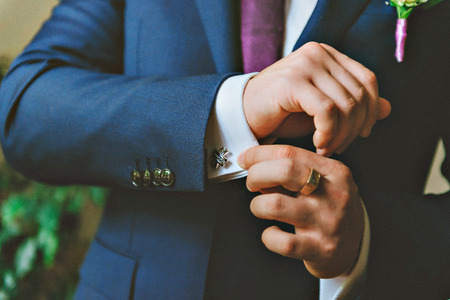 cufflinks: close up of a hand man how wears white shirt and cufflink. The groom button cufflinks on a white shirt Stock Photo
