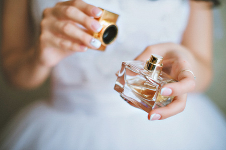 bride applying perfume on her wrist Stock Photo