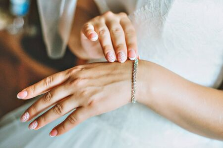 fingers put together: Hands of the bride and white bride dress.