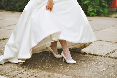 piernas de la mujer de la novia con tacones rojos sentados en un coche, se centran en los zapatos