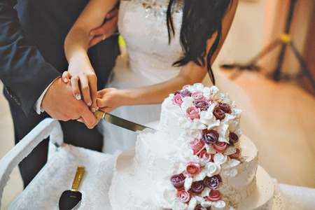 A bride and a groom is cutting their wedding cake  with purple and white flowers. Stock Photo