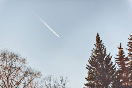 aluminum airplane: Fighter aircraft fuel trace in the turkish blue cloudy sky over trees.
