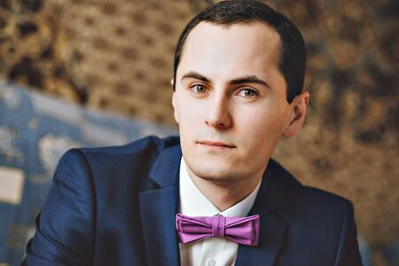 clasping: Studio portrait of young handsome brunette  groom wearing blue suit and purple tie clasping cuff-links. Portrait of a man in a suit. The groom in shirt, jacket and serenity bow tie. Stock Photo