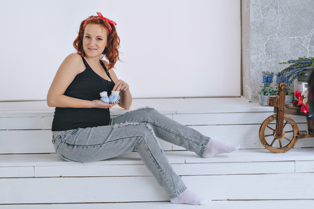 smiing: Happy pregnant woman holding booties, with a red bandage on his head. On a light background. Pregnancy red-haired young woman in a black t-shirt Stock Photo